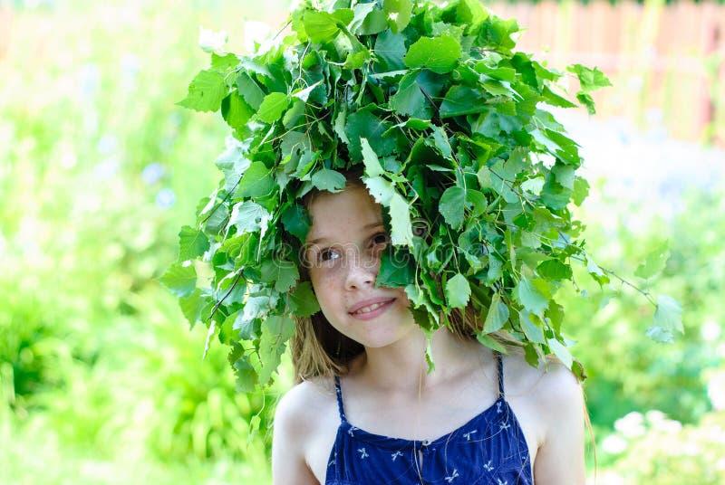 Schönes kleines Mädchen mit einem Kranz von grünen Blättern lizenzfreies stockfoto