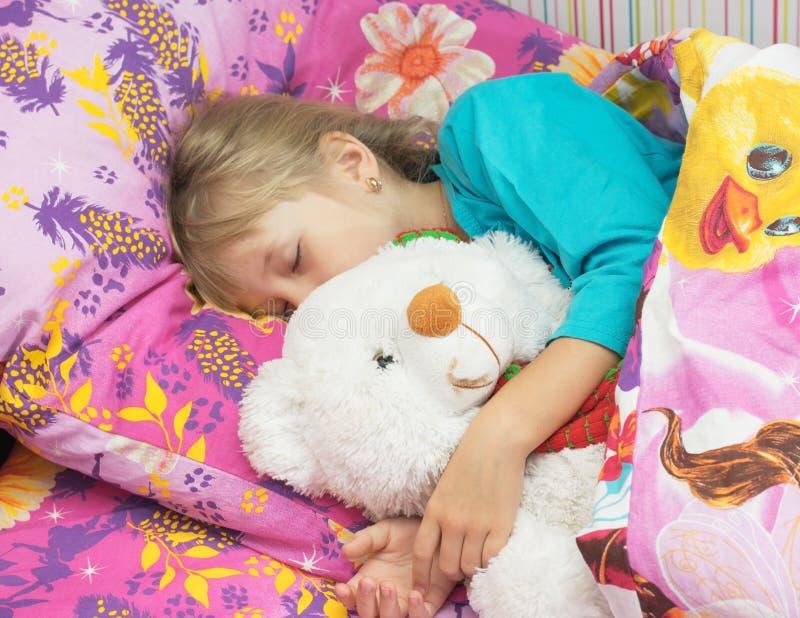 Schönes kleines Mädchen mit einem Spielzeugeisbären stockfotos