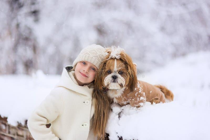 Schönes kleines Mädchen mit ihrem Hund auf dem Schnee im Winter lizenzfreies stockbild