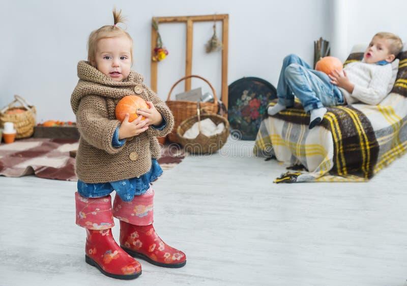 Schönes kleines Mädchen mit Kürbis in den Händen, in den großen Stiefeln und in einer warmen Strickjacke stockfoto