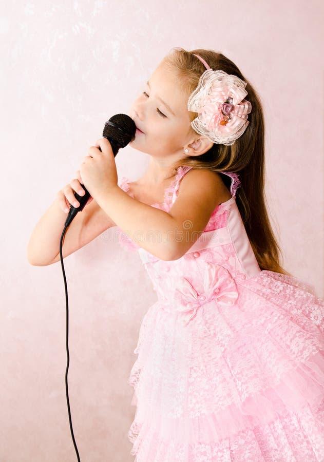 Schönes kleines Mädchen mit Mikrofon in Prinzessinkleid lizenzfreie stockbilder