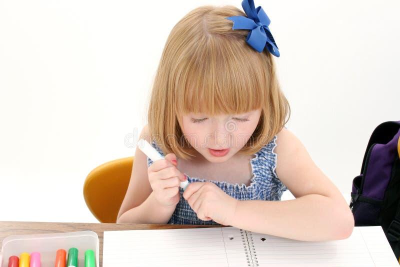 Schönes kleines Mädchen am Schreibtisch mit Kasten der Markierungen und des Notizbuches lizenzfreies stockfoto