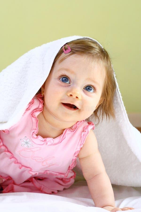 Schönes kleines Mädchen unter weißem Tuch stockfoto