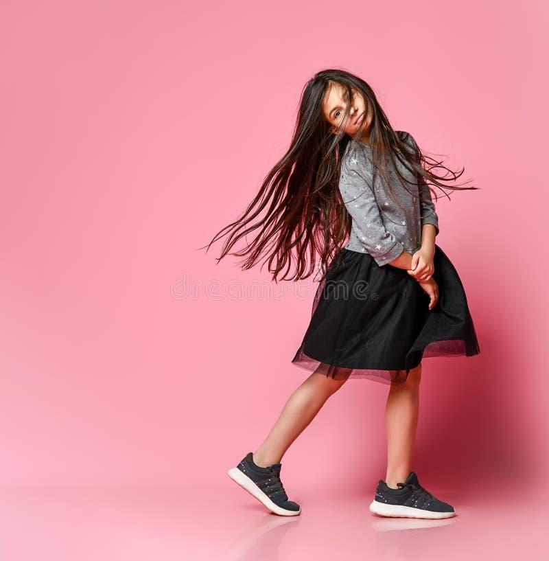 Schönes kleines Mädchen in voller Länge mit langem im grauen Kleid und in den Turnschuhen, die auf einem rosa Hintergrund stehen  stockfotos