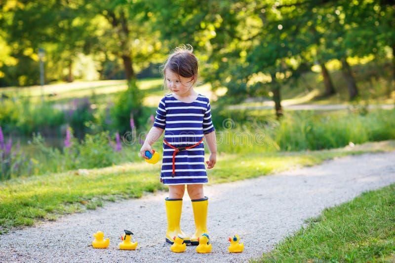 Schönes kleines Mädchen von 2 spielend mit gelben Gummienten in s lizenzfreie stockbilder