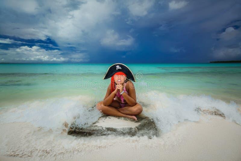 Schönes kleines Piratenmädchen, welches das lustige verärgerte Gesicht, sitzend auf dem tropischen Strand gegen ruhigen Ozean und lizenzfreie stockbilder