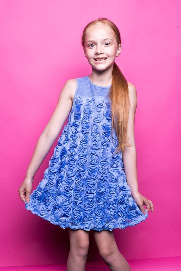 Schönes kleines Rothaarigemädchen im blauen Kleid, das wie Modell auf rosa Hintergrund aufwirft stockfotografie