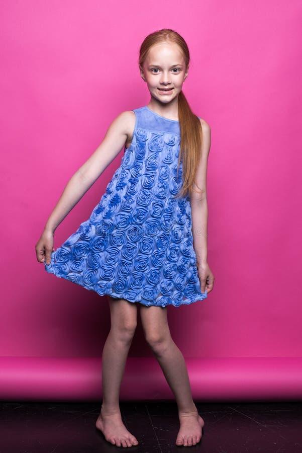 Schönes kleines Rothaarigemädchen im blauen Kleid, das wie Modell auf rosa Hintergrund aufwirft stockfotos