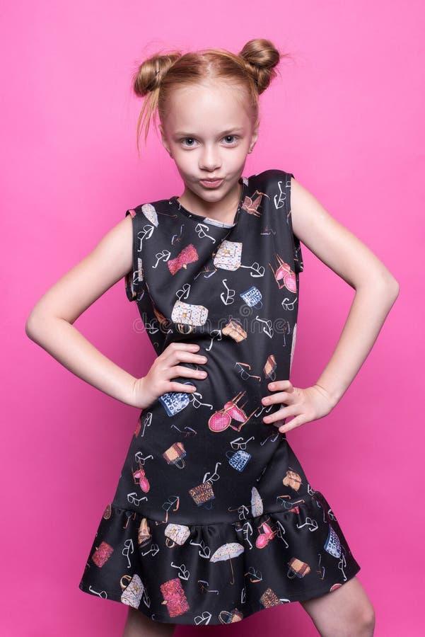 Schönes kleines Rothaarigemädchen im Kleid, das wie Modell auf rosa Hintergrund aufwirft stockfotografie