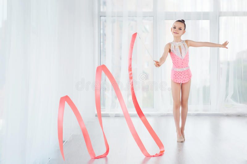 Schönes kleines Turnermädchen im rosa Sportkleidungskleid, Übung der rhythmischen Gymnastik tuend windt sich mit Kunstband stockbild