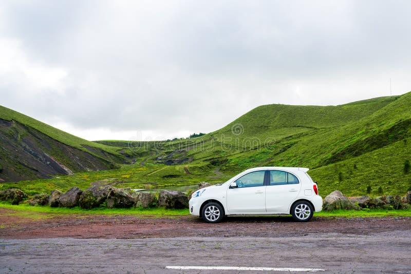 Schönes kleines weißes Auto, welches die Straßenseite bereitsteht stockfotografie