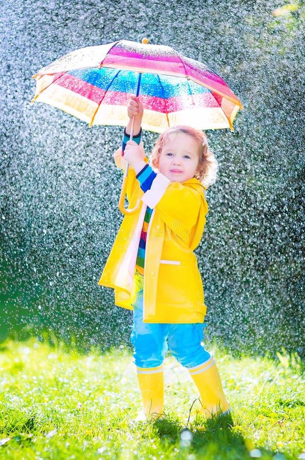 Schönes Kleinkind mit dem Regenschirm, der im Regen spielt lizenzfreie stockfotografie