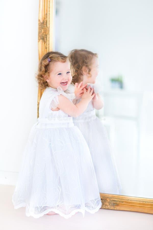 Schönes Kleinkindmädchen im weißen Kleid nahe bei großem Spiegel stockfoto