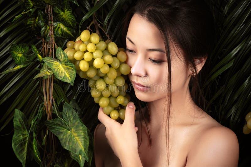 Schönes koreanisches Mädchen des Porträts mit Trauben stockfoto
