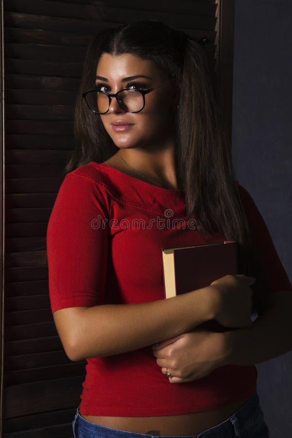 Schönes Kursteilnehmermädchen mit Buch junge Frau in den kurzen Hosen der roten Spitze und des Denims mit Gläsern lizenzfreies stockbild