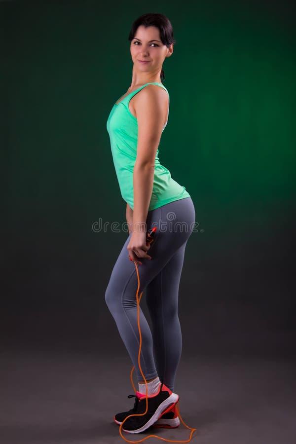 Schönes Lächeln athletisch, Eignungsfrauenstellung, werfend mit einem Seilspringen auf einem grauen Hintergrund mit einer grünen  lizenzfreie stockfotografie