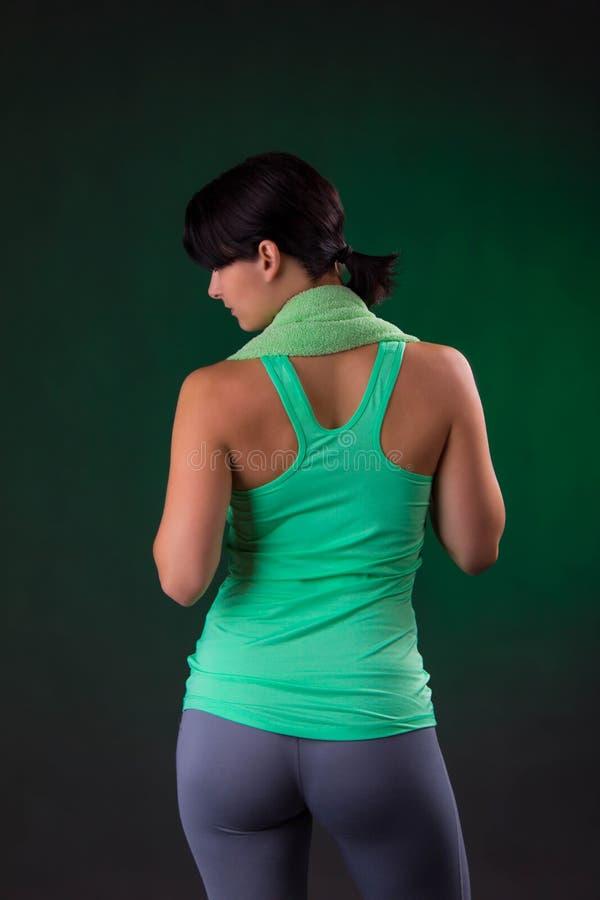 Schönes Lächeln athletisch, Eignungsfrauenstellung, werfend mit einem Tuch auf einem grauen Hintergrund mit einer grünen Hintergr lizenzfreie stockfotografie