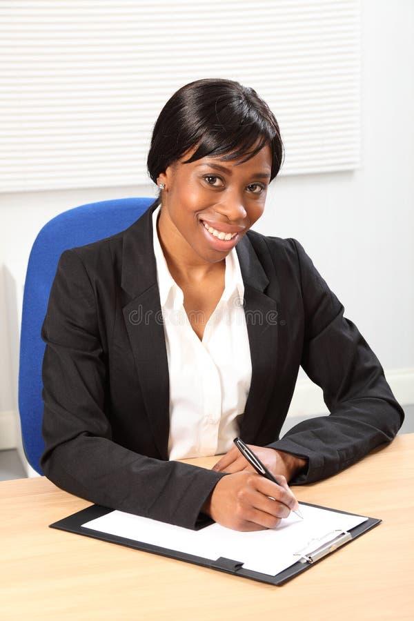 Schönes Lächeln durch schwarze Frau im Geschäftslokal stockfotografie