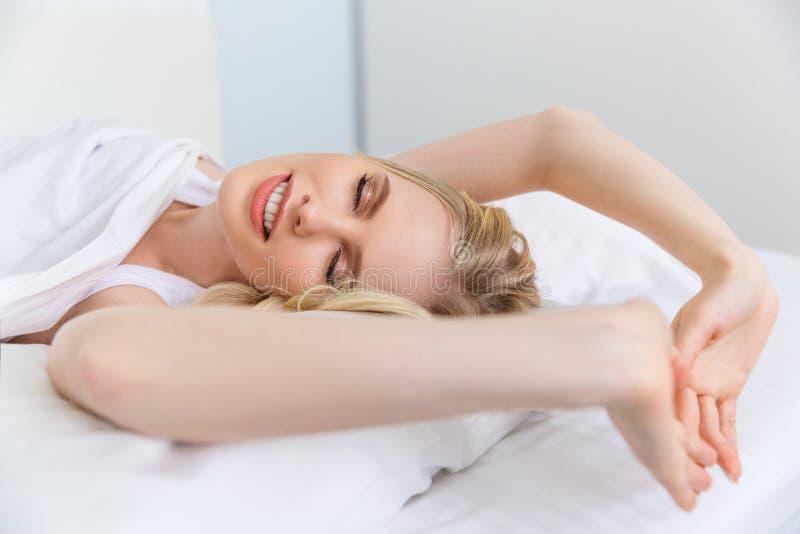 schönes lächelndes blondes ausdehnendes und aufwachendes Mädchen stockbilder