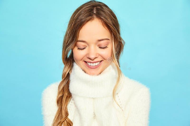 Schönes lächelndes blondes herrliches Mädchen Frauenstellung in der stilvollen weißen Strickjacke stockfotos