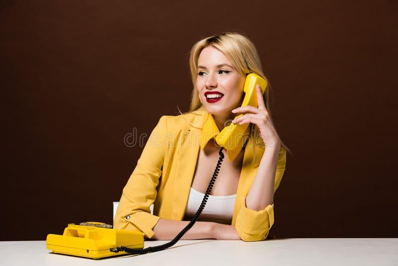 schönes lächelndes blondes Mädchen, das per Weinlesetelefon spricht und weg schaut stockbilder