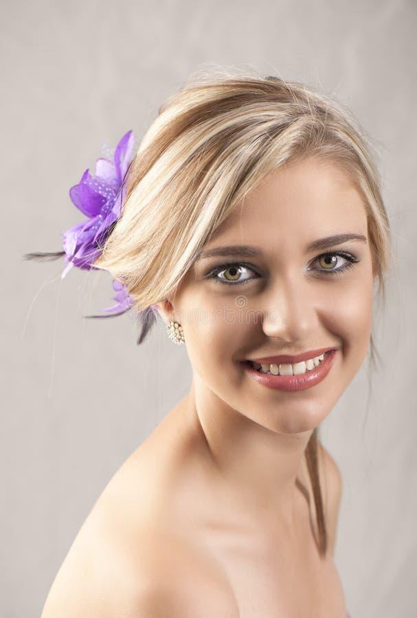 Schönes lächelndes blondes Mädchen mit purpurroter Blumen-Haarspange lizenzfreie stockfotografie