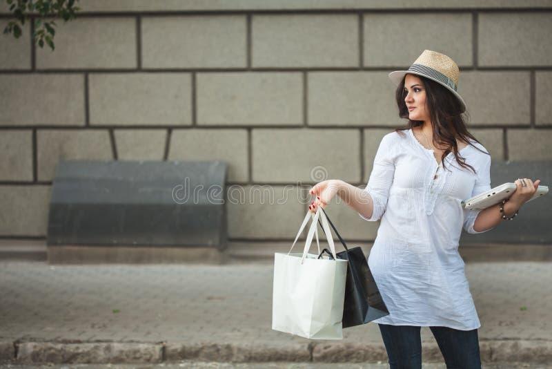 Schönes lächelndes Brunettemädchen in einem Hut gehend hinunter die Straße mit Laptop und Paketen von einem Speicher stockfotografie
