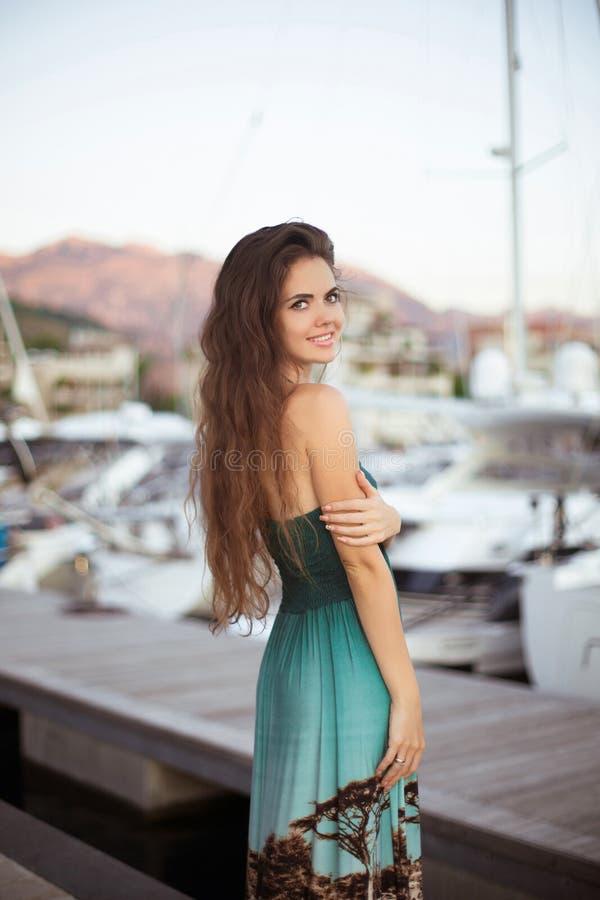 Schönes lächelndes Brunettemädchen mit dem langen Haar, das durch Yachten aufwirft stockfotografie