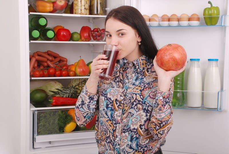 Schönes lächelndes junges Mädchen hält ein Glas Granatapfelsaft und -granat stockfotos