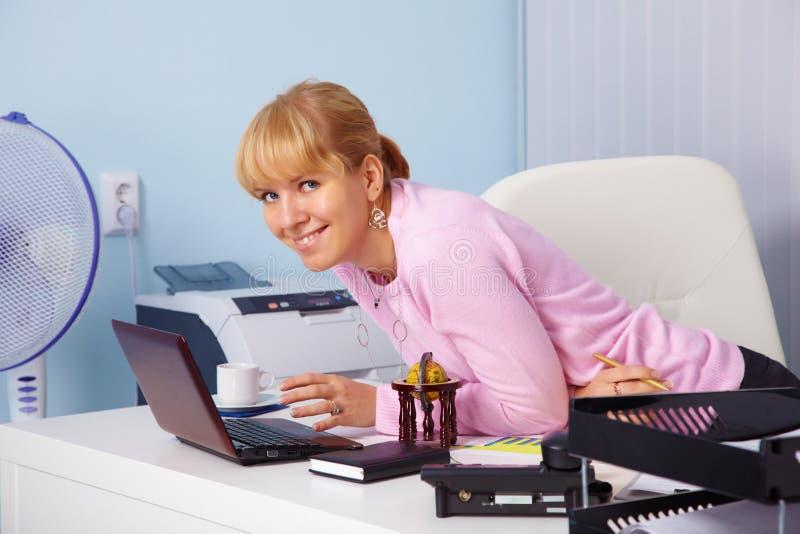 Schönes lächelndes junges Mädchen im Büro lizenzfreie stockbilder