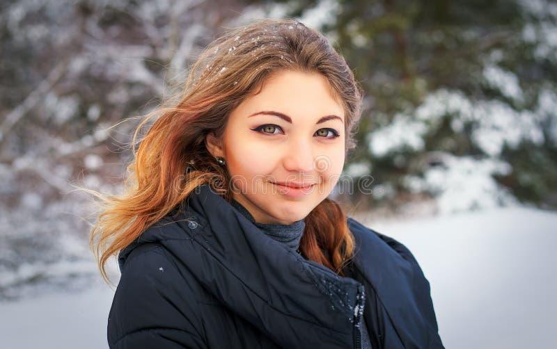 Schönes lächelndes junges Mädchen im Winter im kalten Wald stockfoto