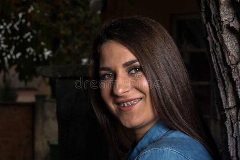 Schönes lächelndes junges Mädchen mit den Klammern, die an einem Baum mit Kopienraum auf schwarzem Hintergrund sich lehnen lizenzfreie stockfotos