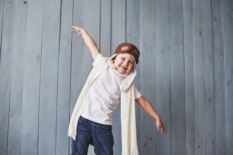 Schönes lächelndes Kind im Sturzhelm auf einem blauen Hintergrund, der mit einer Fläche spielt Weinleseversuchskonzept stockfoto