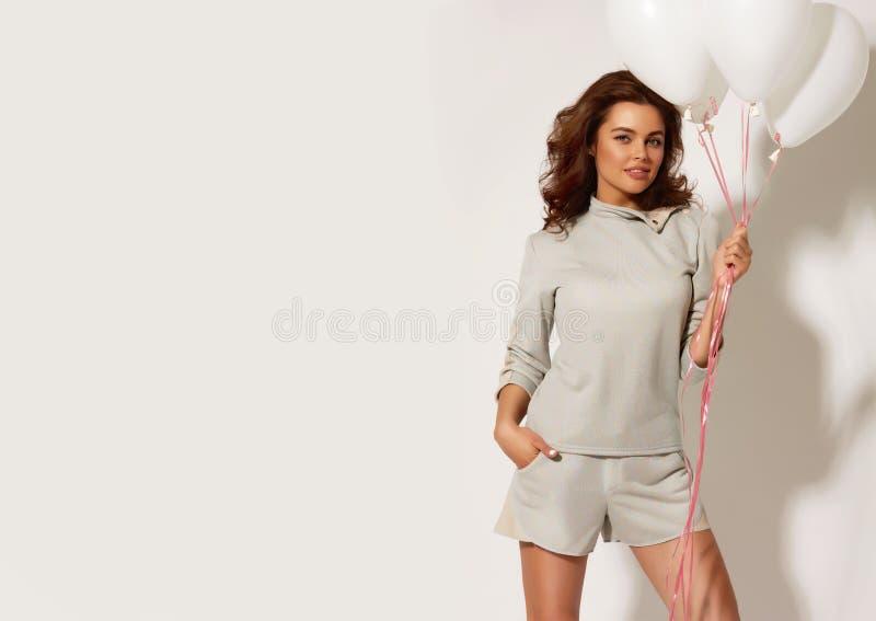 Schönes lächelndes Mädchen, das weiße Ballone auf einem weißen Hintergrund am Studio hält stockfoto