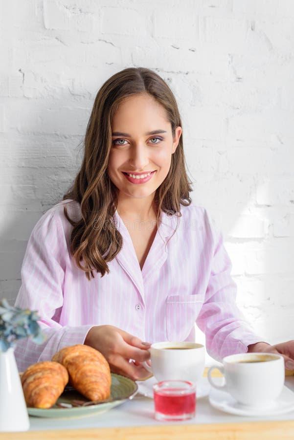 schönes lächelndes Mädchen in den rosa Pyjamas, die im Bett frühstücken stockfotografie