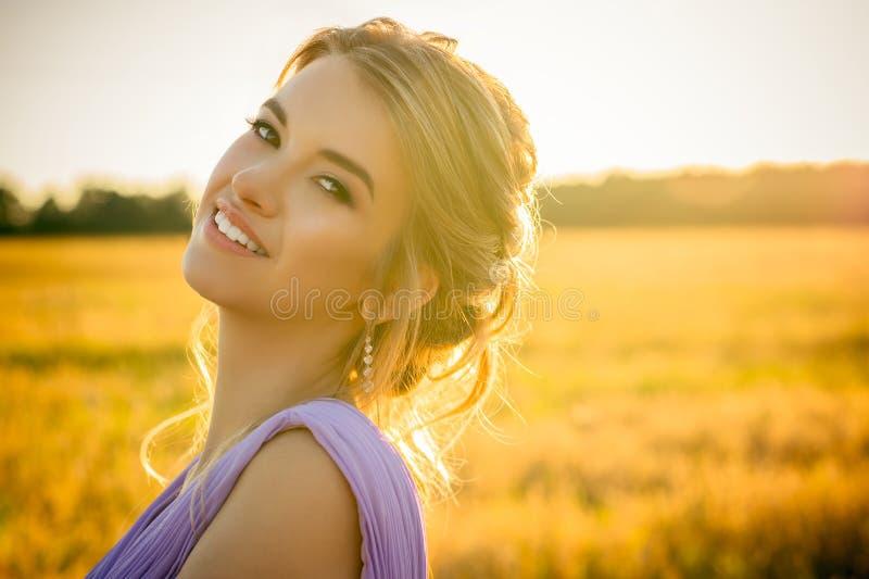 Schönes lächelndes Mädchen des Porträts auf Sonnenuntergang lizenzfreie stockfotografie