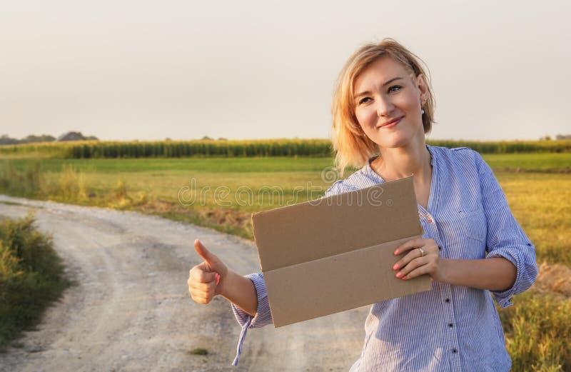Schönes lächelndes Mädchen erhält per Anhalter gefahren und wählt mit einem Zeichen von Autos auf einer Landstraße in den Strahle stockfoto