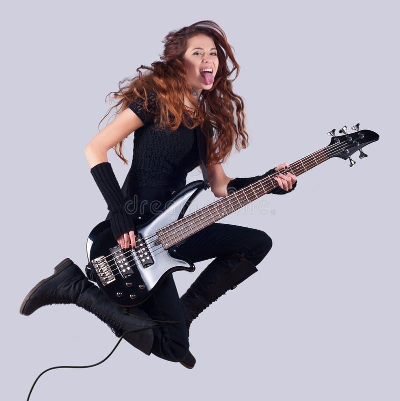 Schönes lächelndes Mädchen mit Bass-Gitarre stockfotos