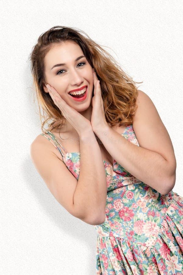 Schönes lächelndes Mädchen mit dem langen Haar und blumigem Kleid lizenzfreie stockfotografie