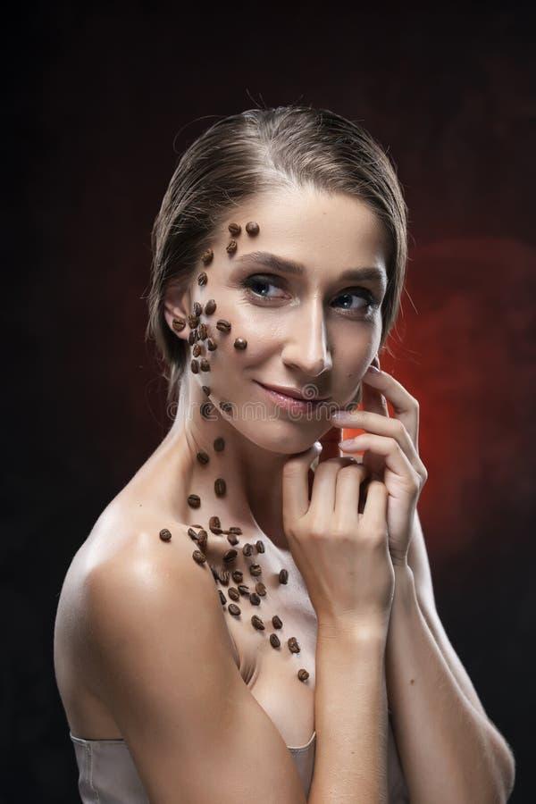 Schönes lächelndes Mädchen mit nackten Schultern berührt ihr Gesicht mit ihren Händen Kaffeebohnen wurden künstlerisch an ihrem g lizenzfreie stockfotografie