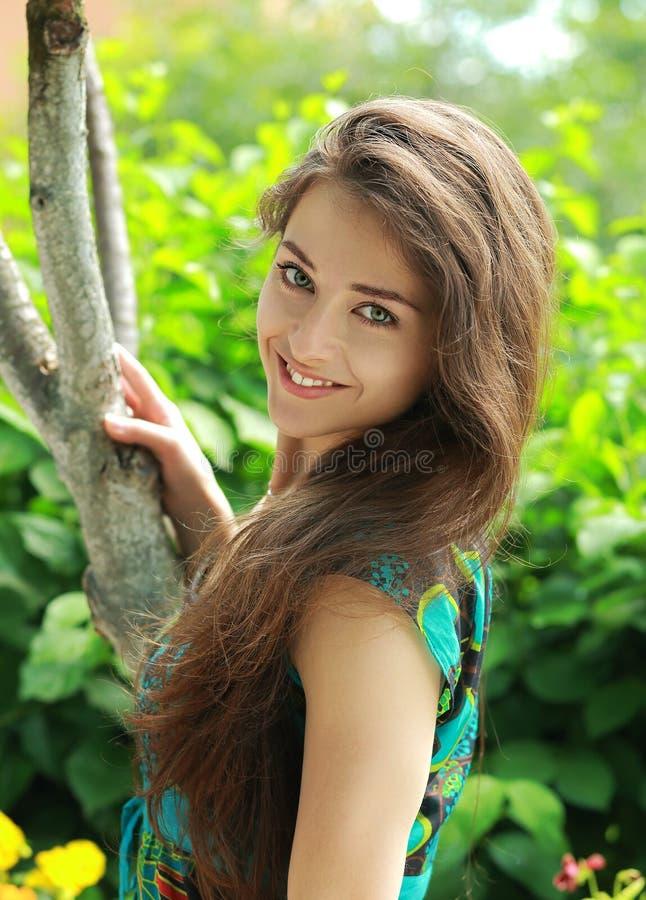 Schönes lächelndes Mädchen nahe Baum stockfotos