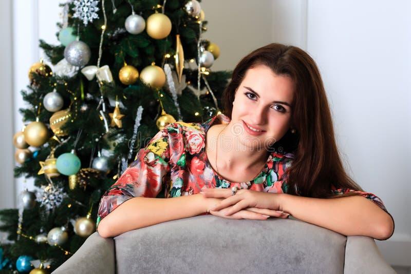 Schönes lächelndes Mädchen nahe einem Weihnachtsbaum lizenzfreie stockfotografie