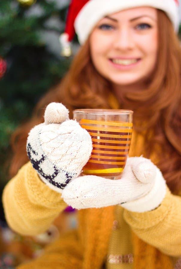 Schönes lächelndes Mädchen nahe Weihnachtsbaum mit Schale stockfoto