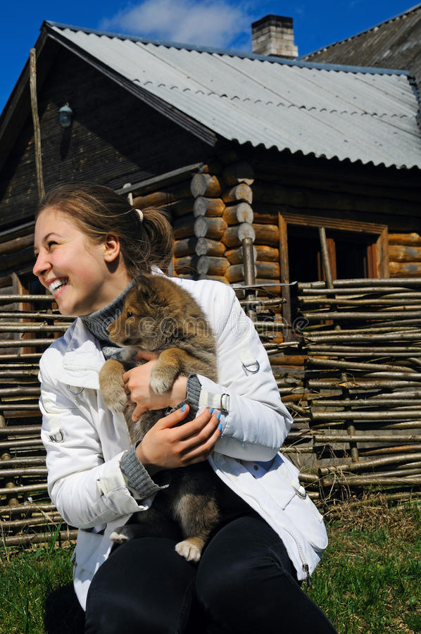 Schönes lächelndes Mädchen pets einen Welpen stockfotos