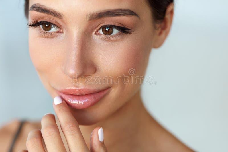 Schönes lächelndes Mädchen Schönheits-rührende Lippen mit Lippenbalsam an stockfoto