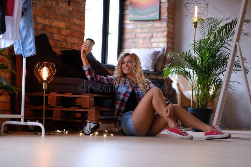 Schönes lächelndes Mädchen sitzt nahe bei dem Palettensofa mit Tasse Kaffee stockbild