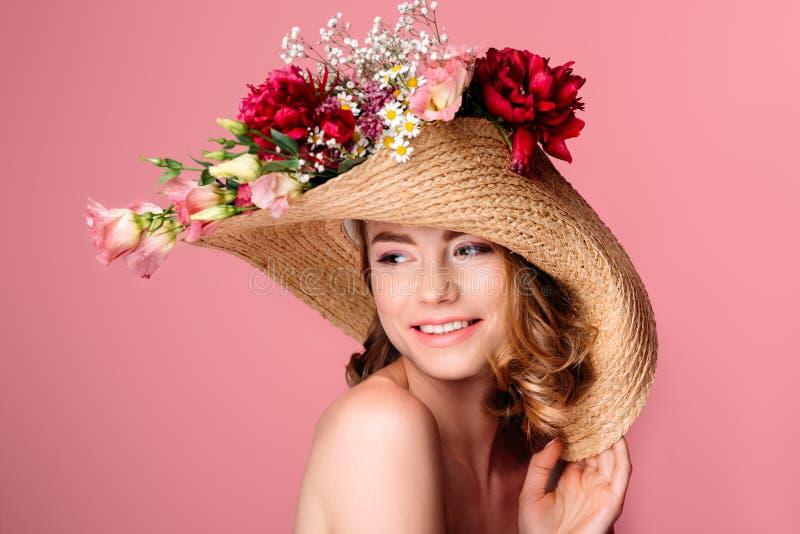schönes lächelndes nacktes Mädchen, das Weidenhut mit Blumen trägt stockfotos