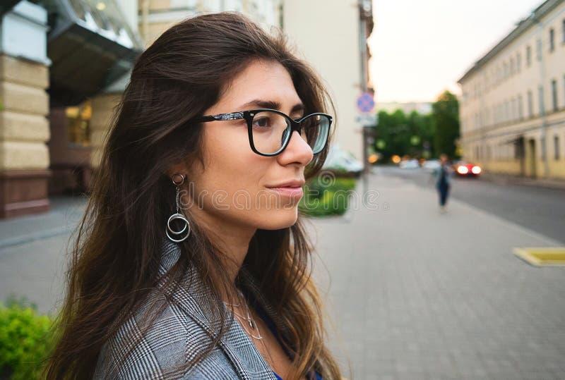 Schönes lächelndes nettes Gehen der jungen Frau auf die Straße an einem sonnigen Tag, zufälliges hübsches Mädchen an der Stadt lizenzfreies stockbild