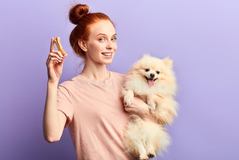Schönes lächelndes rothaariges Mädchen, das entzückendes Haustier und Knochen hält lizenzfreie stockfotografie