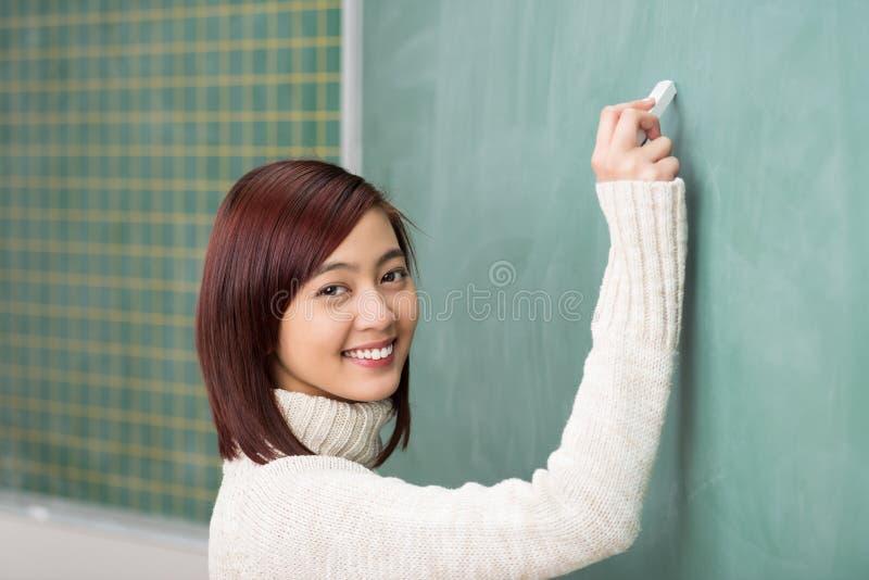 Schönes lächelndes Studentenschreiben auf einer Tafel lizenzfreies stockfoto